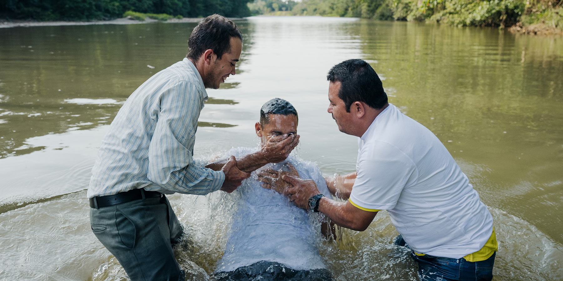 Person being baptized in a river.
