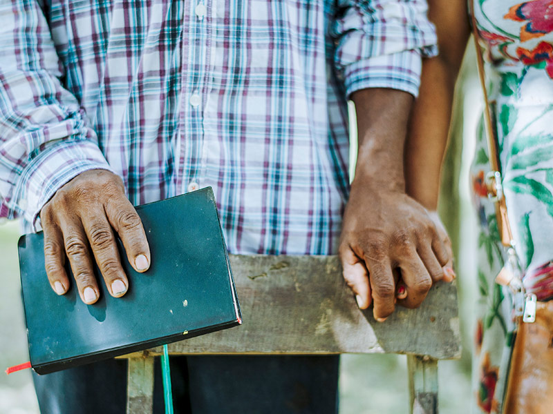 Couple holding hands and holding a Bible