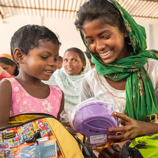Two girls looking through contents of backpack