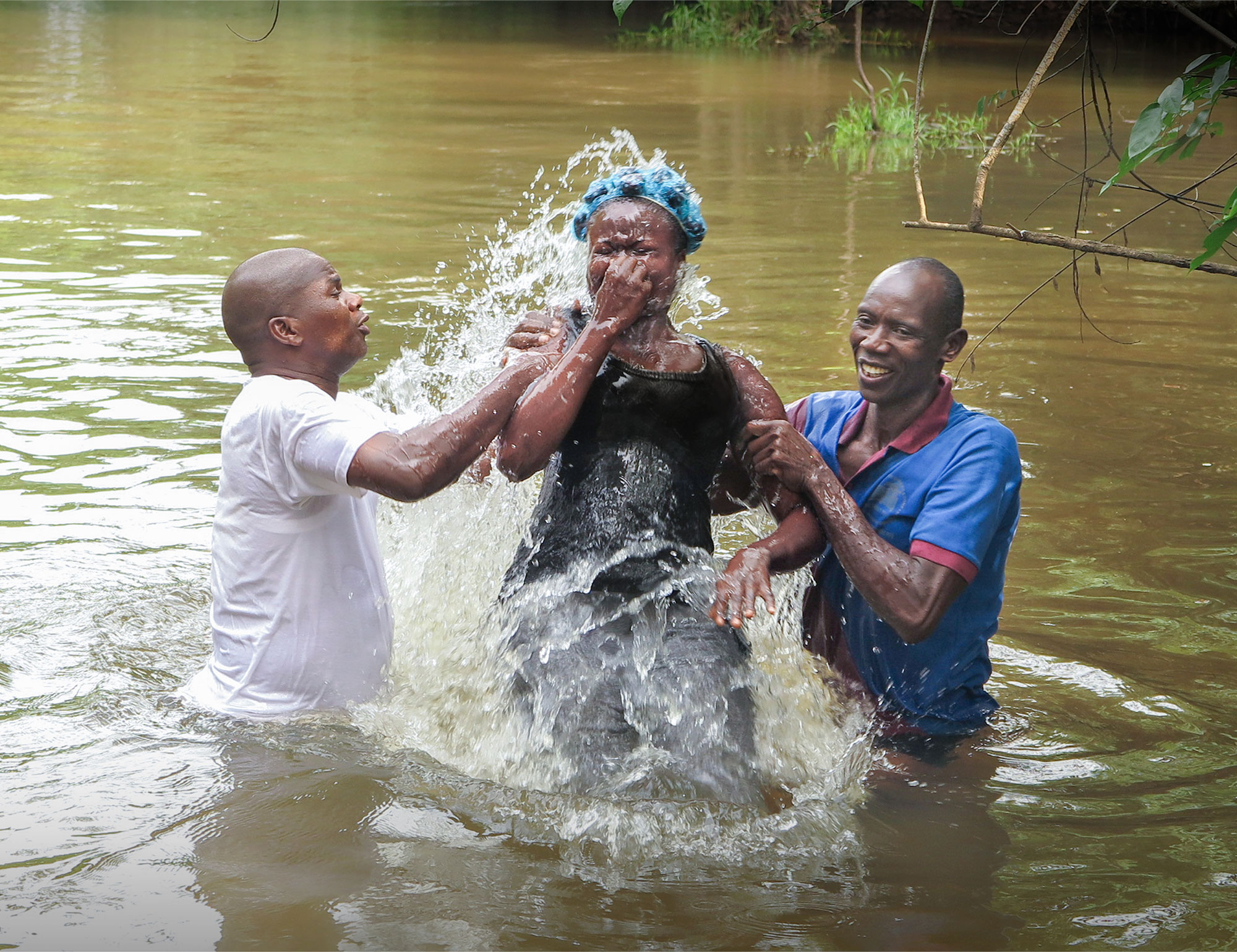 Two men helping a woman through baptism in a body of water