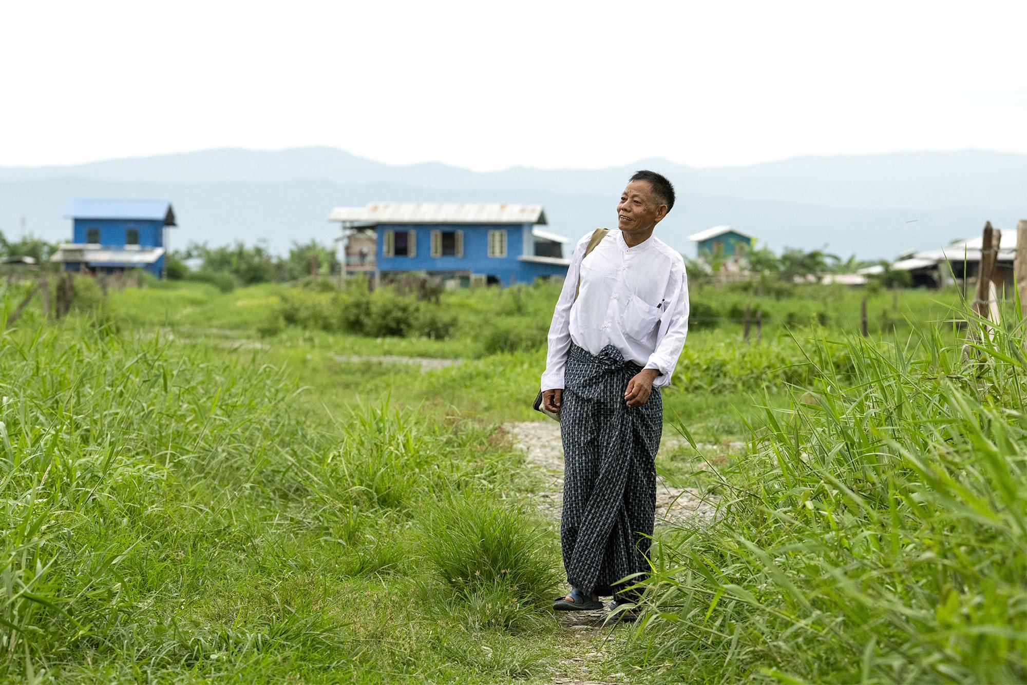 Man walking a grassy trail, looking hopeful