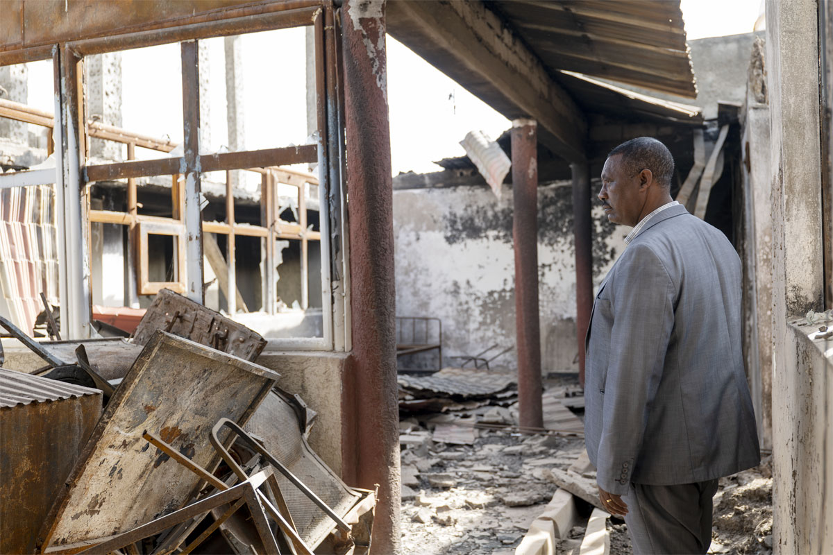 A pharmacist examines the remains of his pharmacy and clinic, which were destroyed by Islamic extremists
