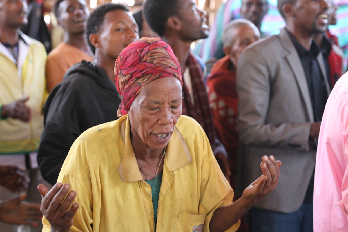 An Ethiopian woman worships in a church building that has been attacked in the past