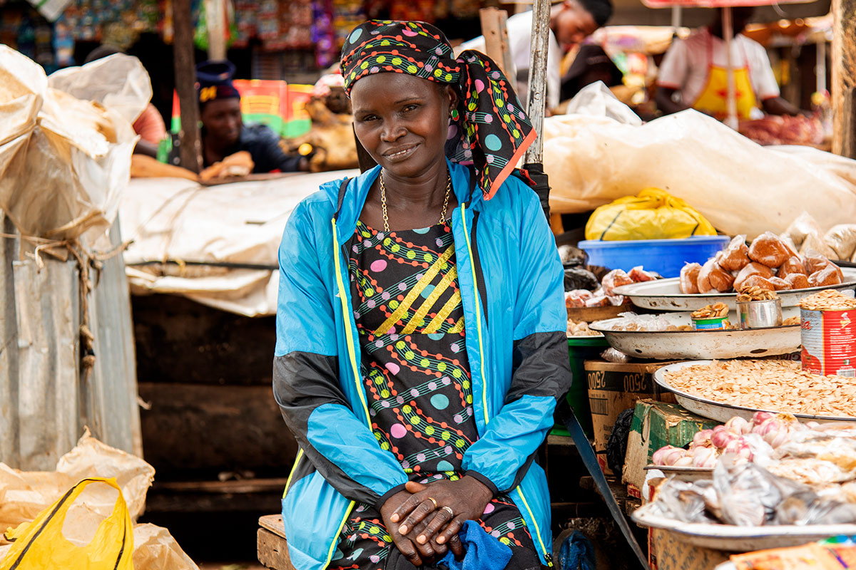 Woman with blue jacket sitting in market