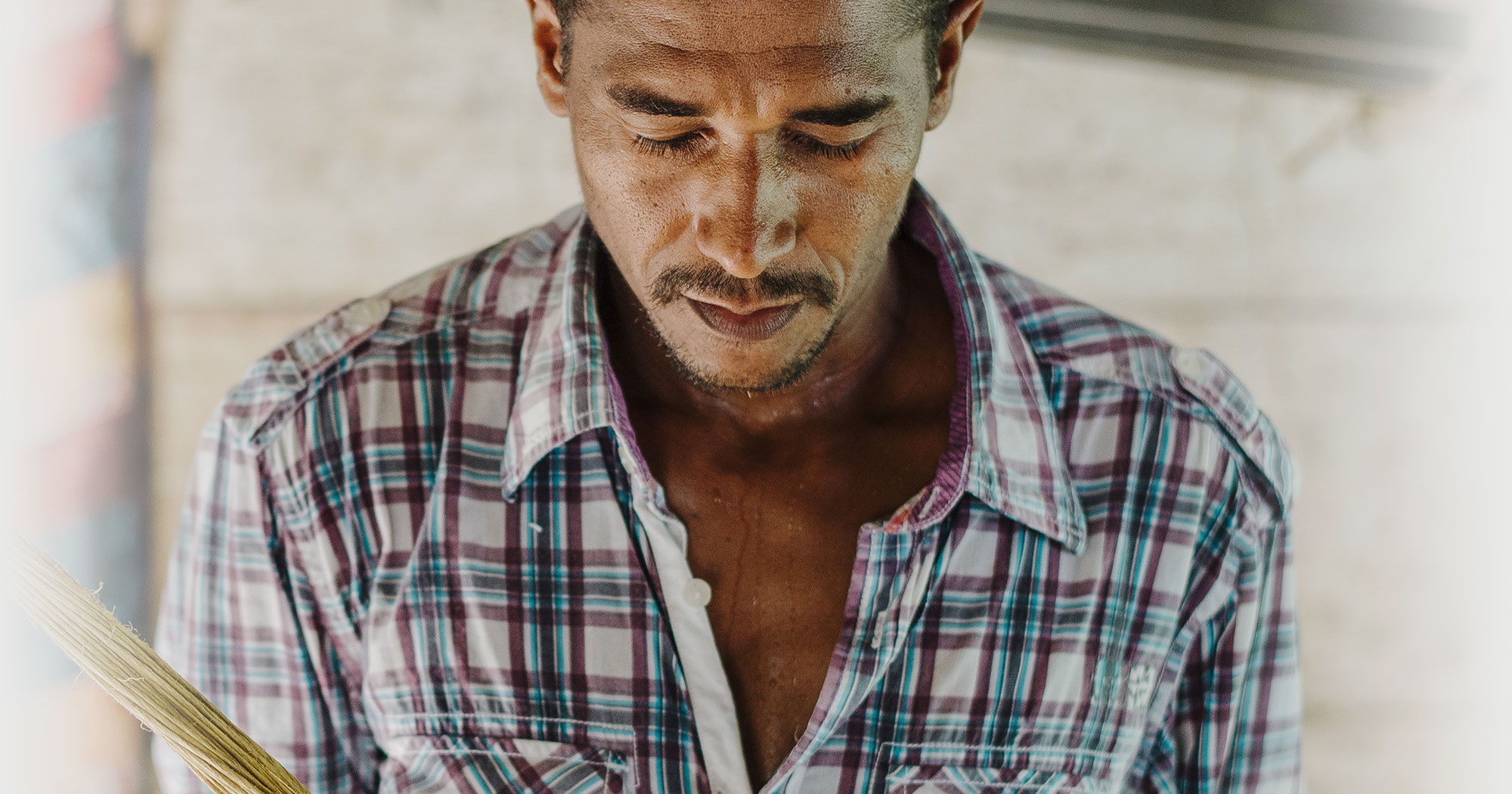 Man with eyes closed and head tilted in plaid shirt down praying