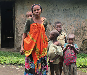 Woman with four children in front of house