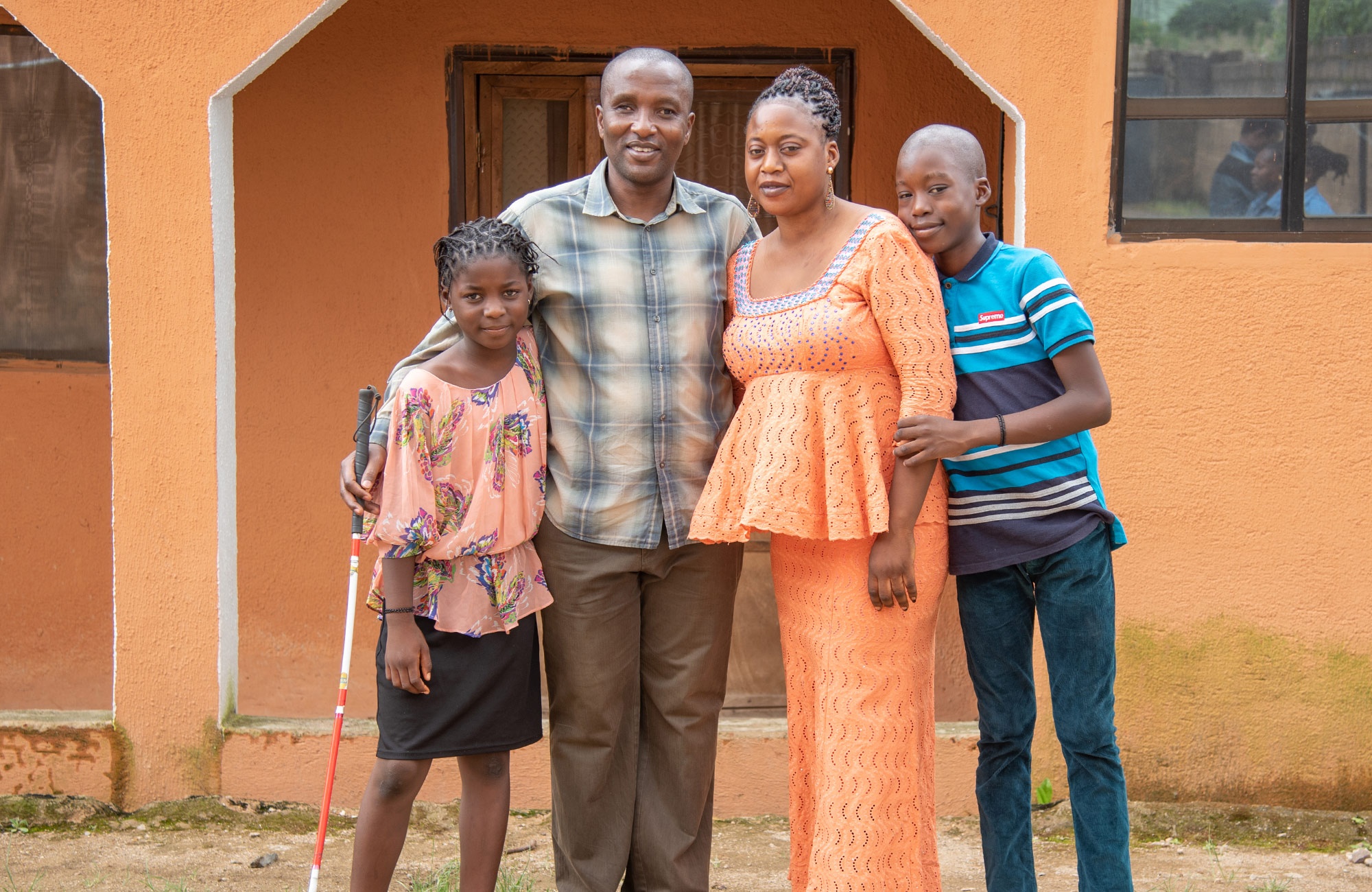 Nigerian Family standing in front of a peach colored building