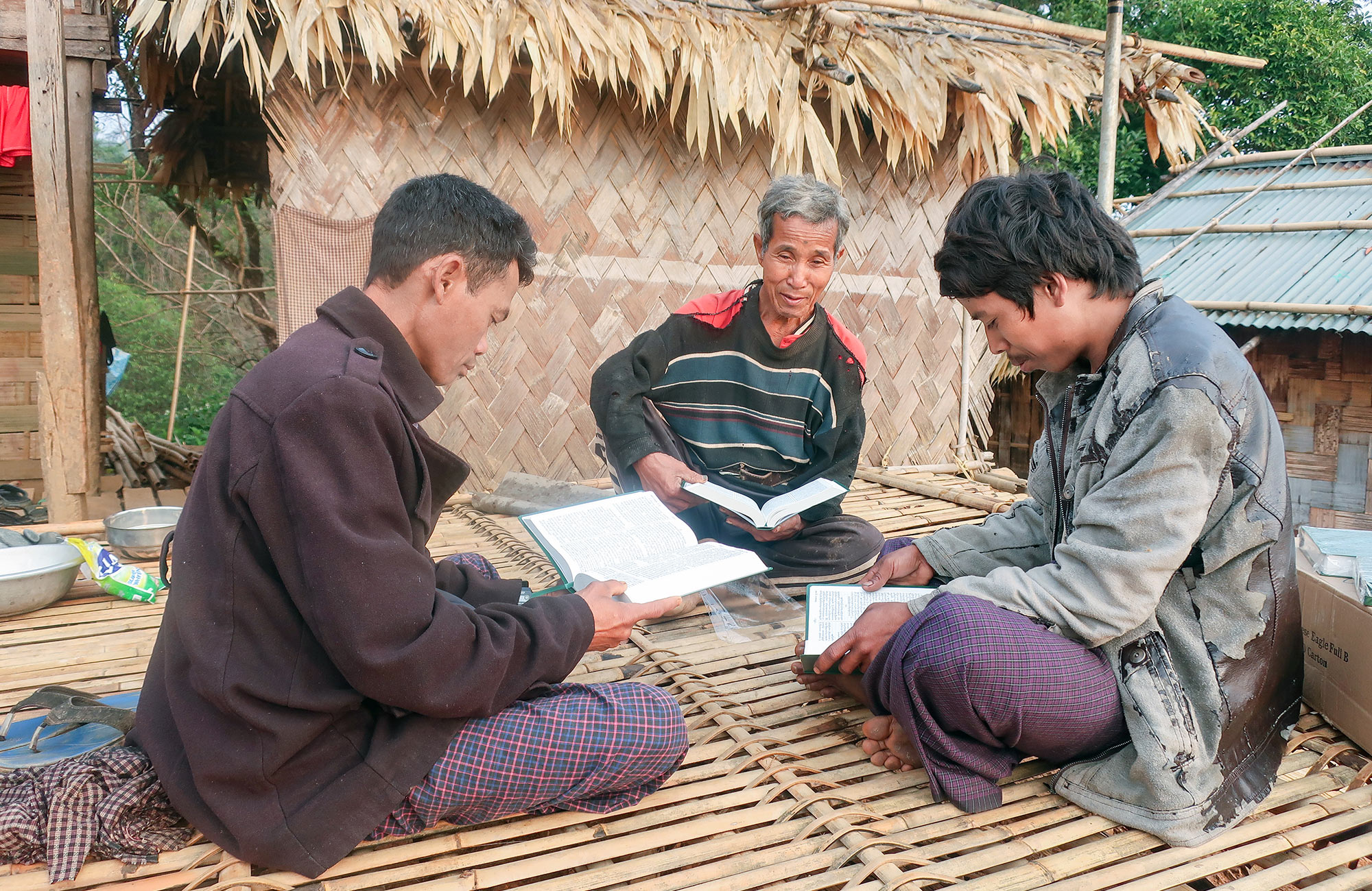 Three men sitting and reading Bibles