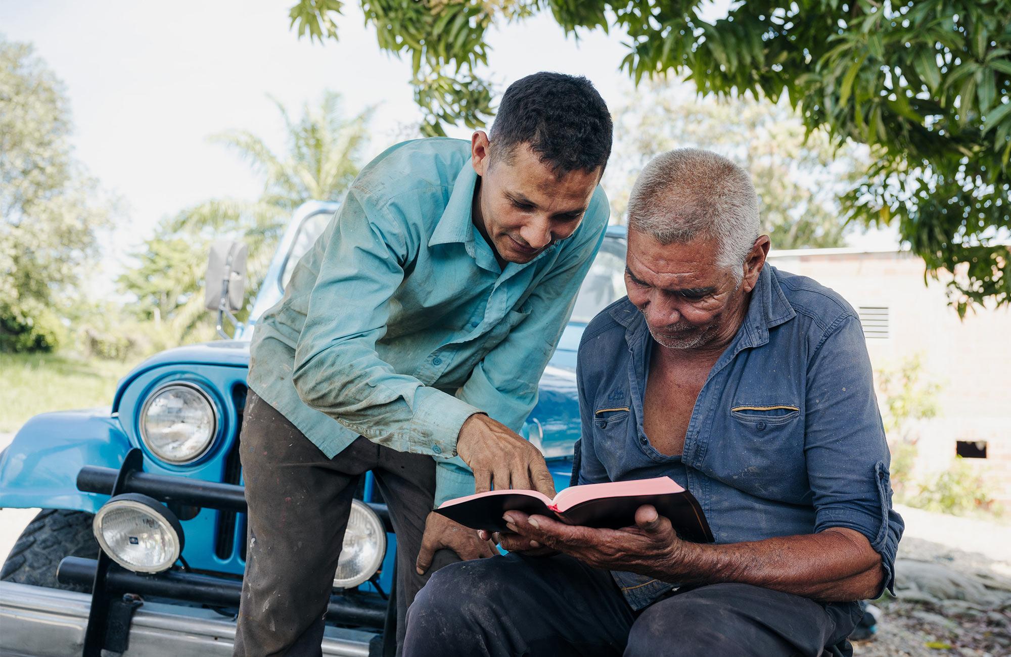 Two men reading a bible.