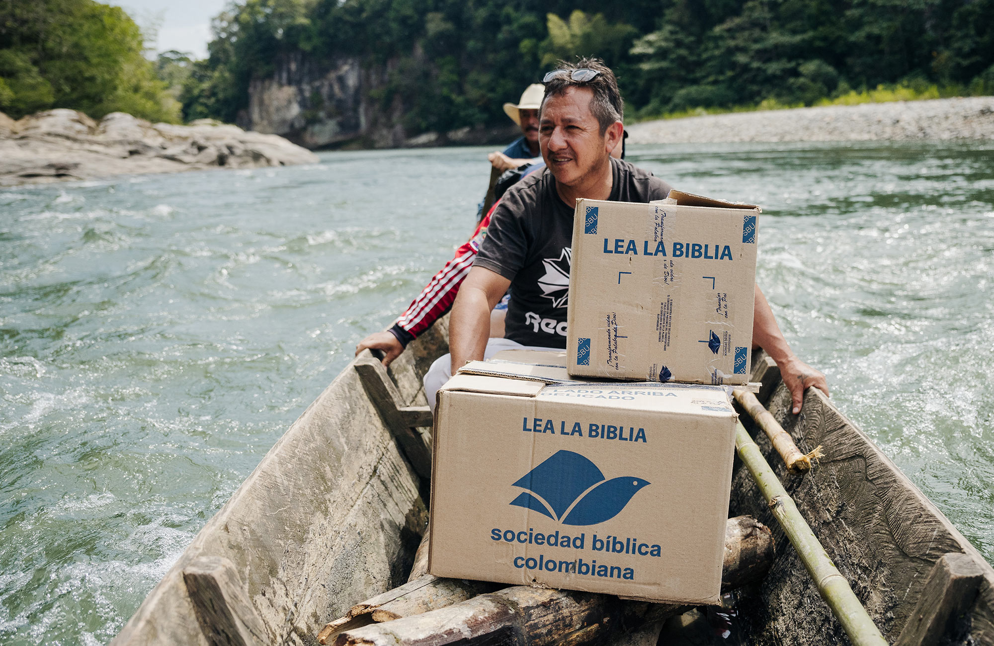 People in canoe transporting boxes of Bibles.