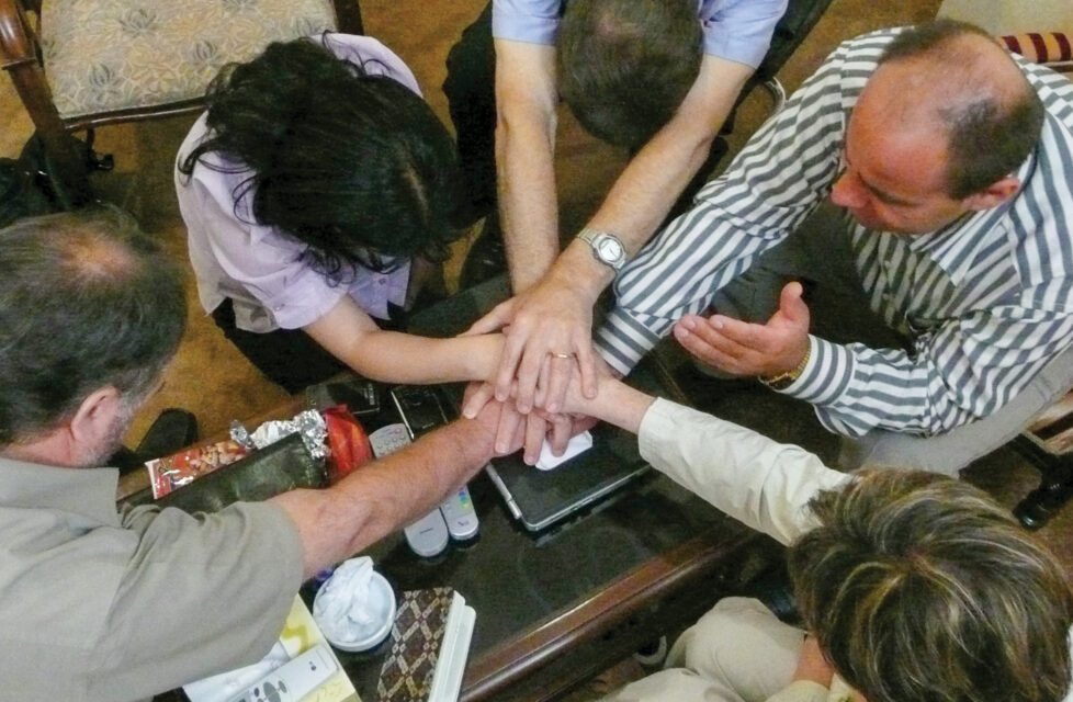 A group of people sit together and pray