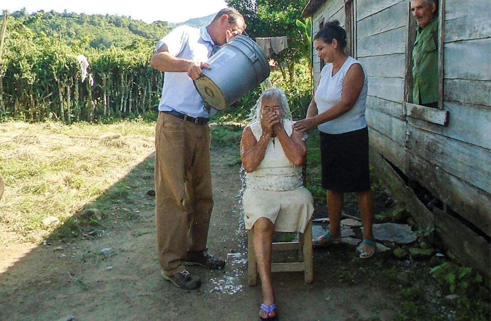 A man pours water over the head of a woman for baptism