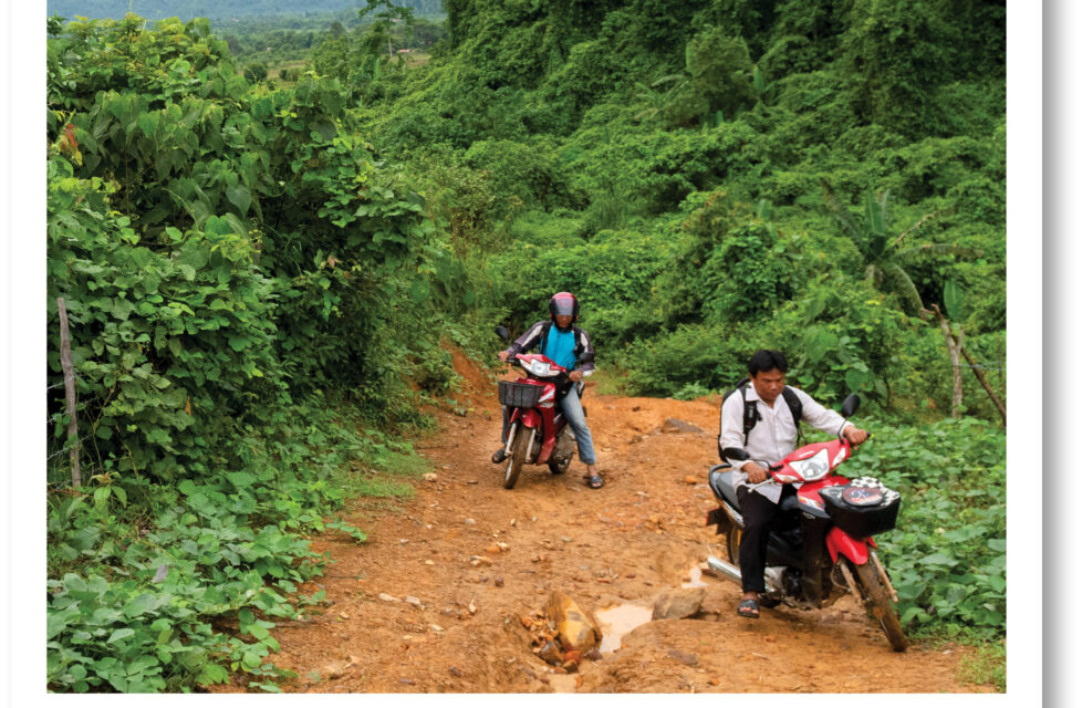Two men riding motorbikes up a hill