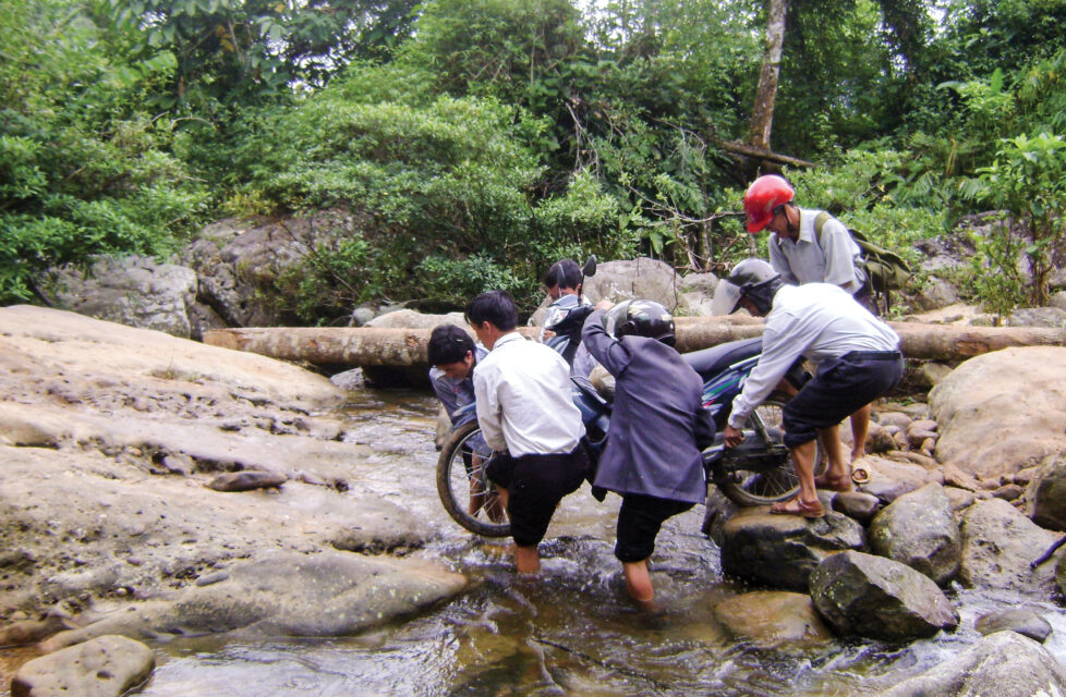 men help carry motorcycle across stream