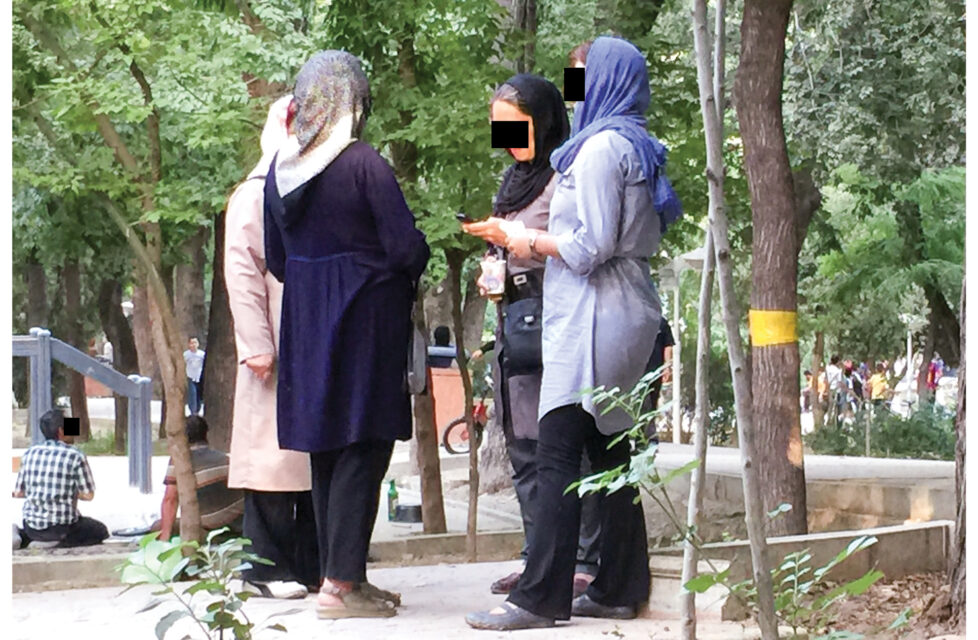 a group of women stand together outside talking with black boxes over their eyes