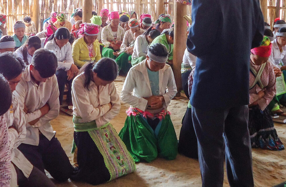 A Man standing in front of his congregation while they pray